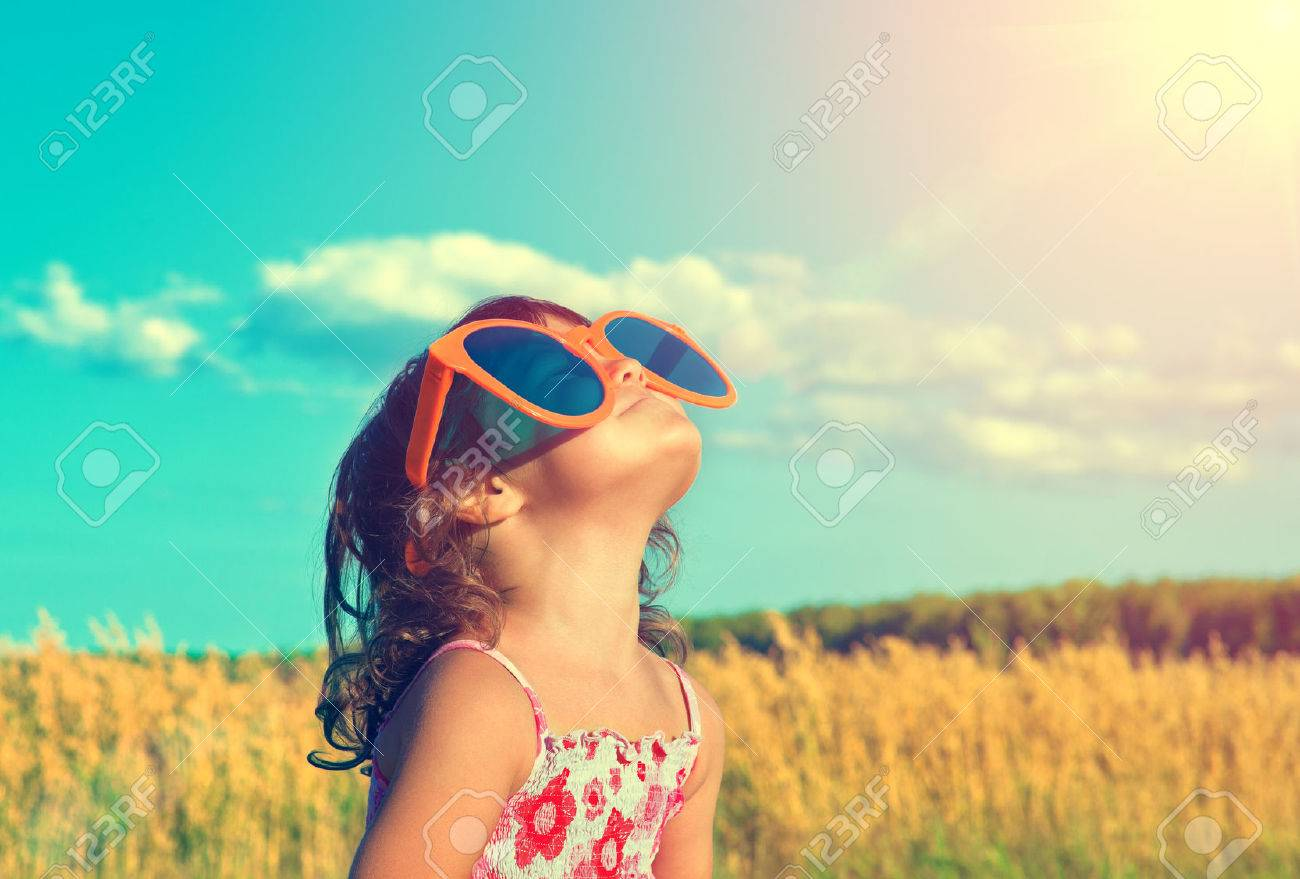 Happy little girl with big sunglasses looking at the sun - 32517410