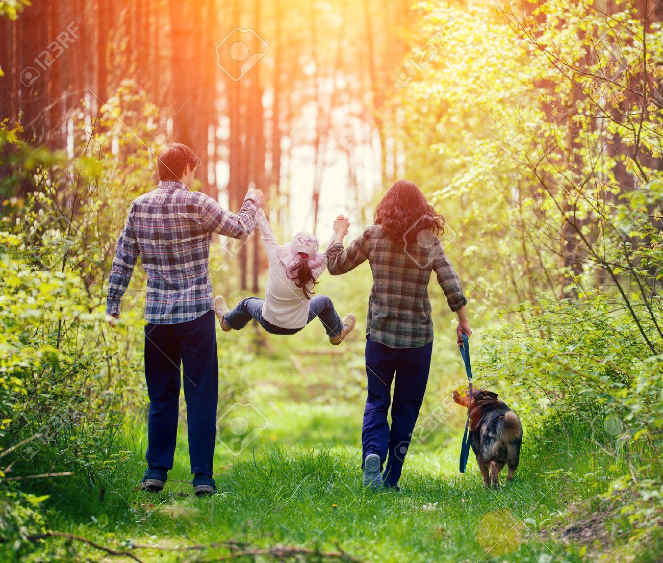 Banque dimages happy family marcher avec le chien dans la forêt
