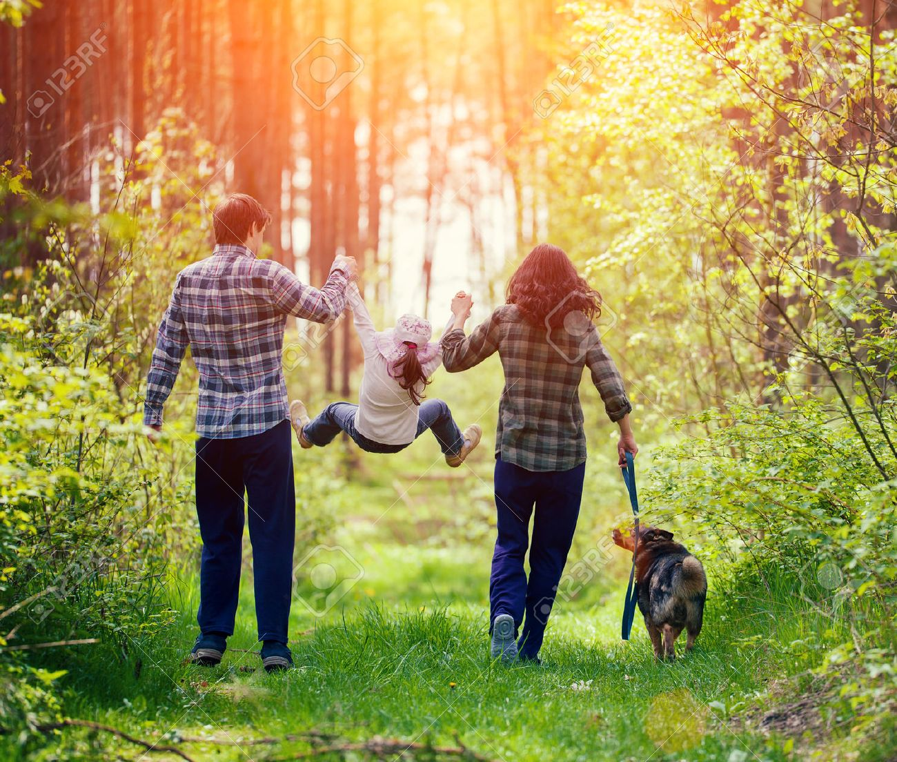 Happy Family Walking With Dog In The Forest Stock Photo