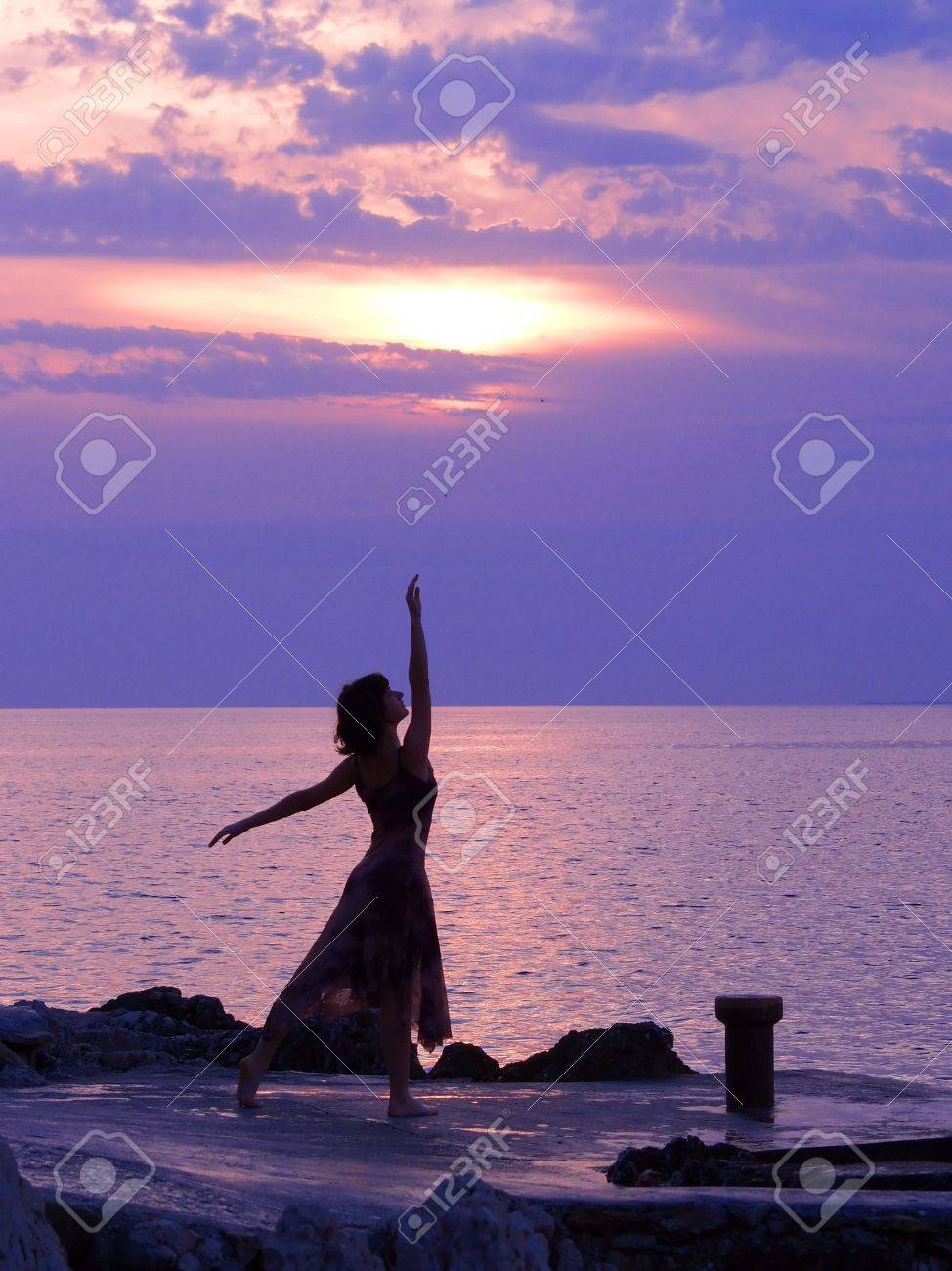 Young woman standing at ballerina pose, sunset at the background Stock Photo - 578465