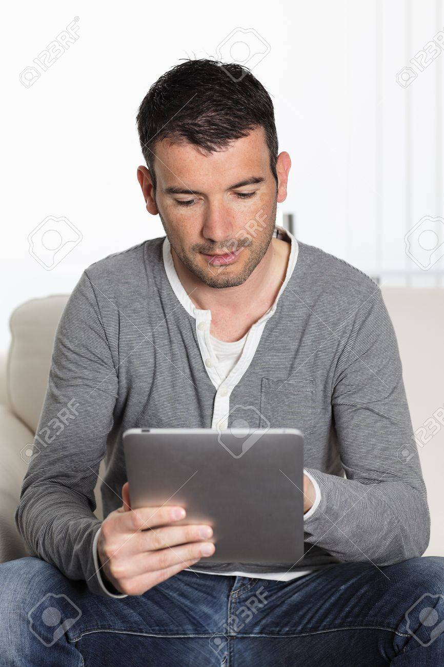 man using tablet pc sitiing on sofa at home Stock Photo - 9611345