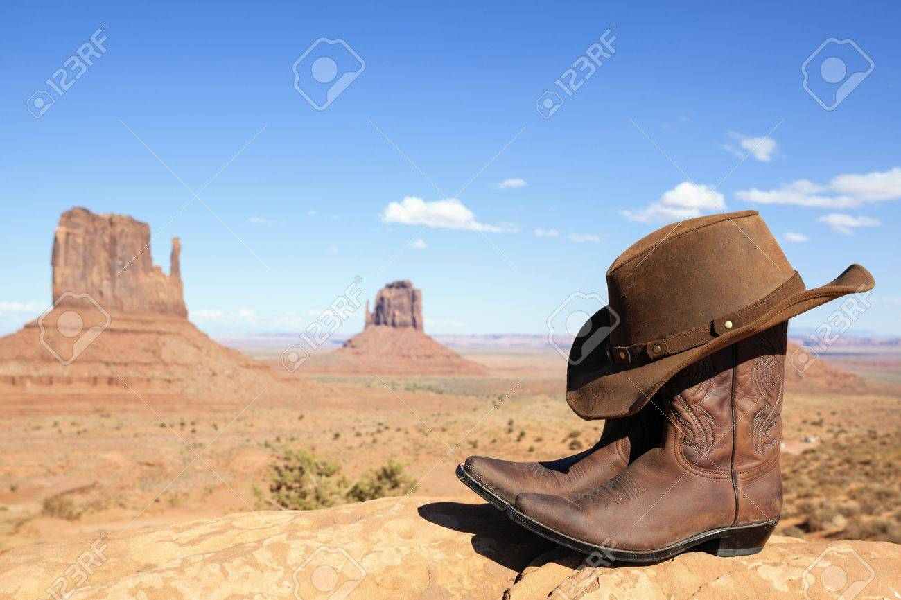 cowboy boots and hat in front of Monument Valley, USA, panoramic..