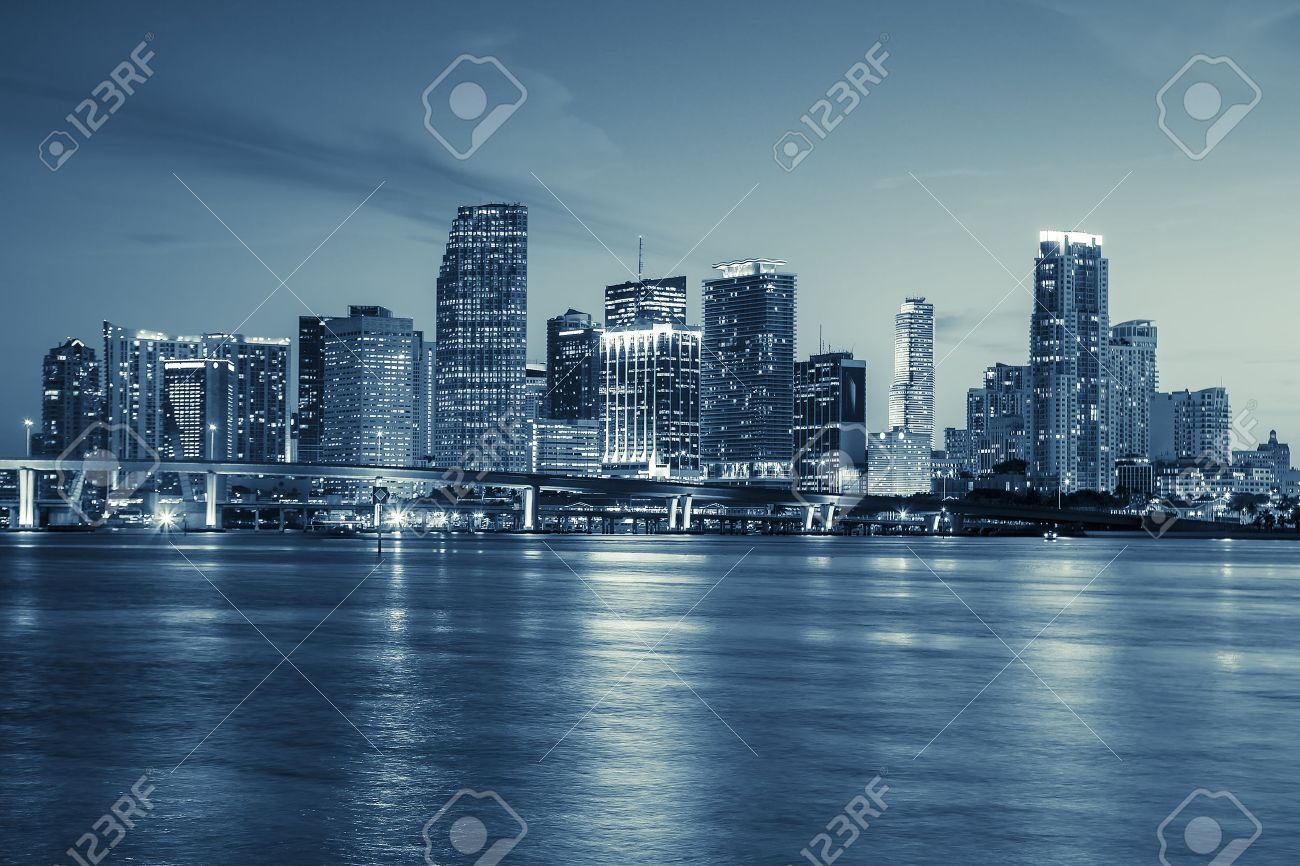 Miami skyline panorama at dusk with urban skyscrapers and bridge over sea with reflection - 31899177