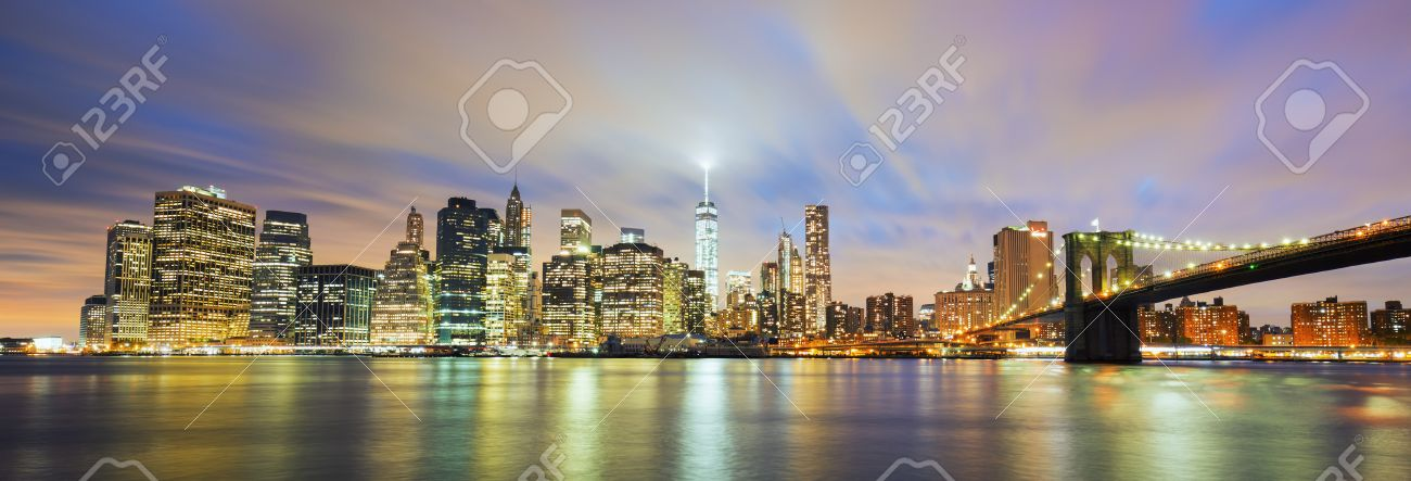 Panoramic view of New York City Manhattan midtown at dusk with skyscrapers illuminated over east river - 46779385