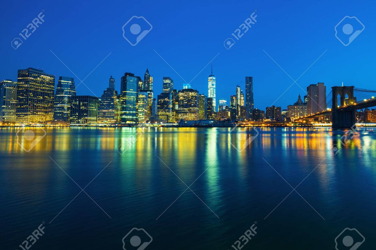 New York City Manhattan midtown at dusk with skyscrapers illuminated over east river - 52032288