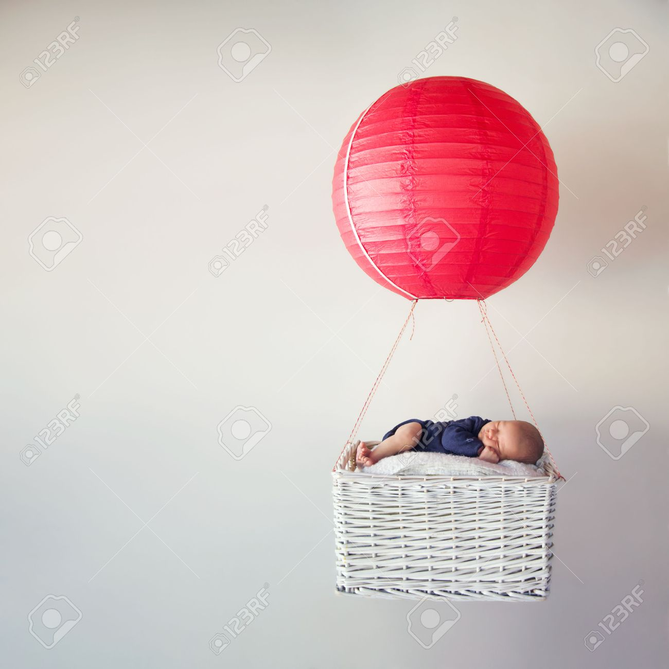 Newborn baby sleeping in a tiny basket of an air balloon - 57645056