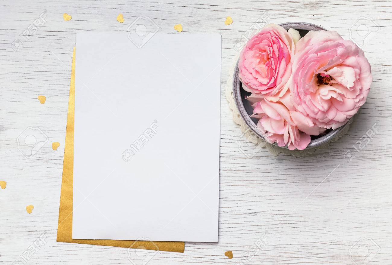 Blank paper and cute pink flowers on white wooden table top stock blank paper and cute pink flowers on white wooden table top view stock photo mightylinksfo