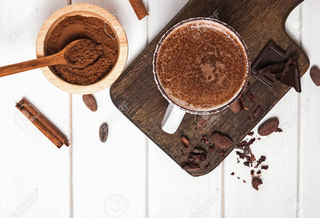 Hot chocolate in the cup, cocoa beans and powder on the white wooden table - 118170615