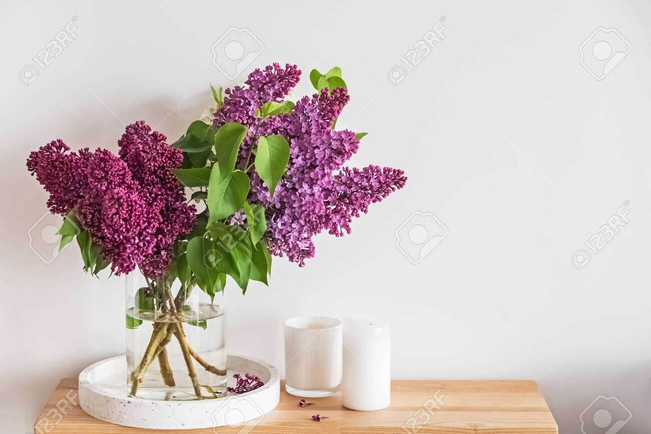 Bouquet of beautiful lilac flowers standing in a glass vase on the small wooden stand - 122694664