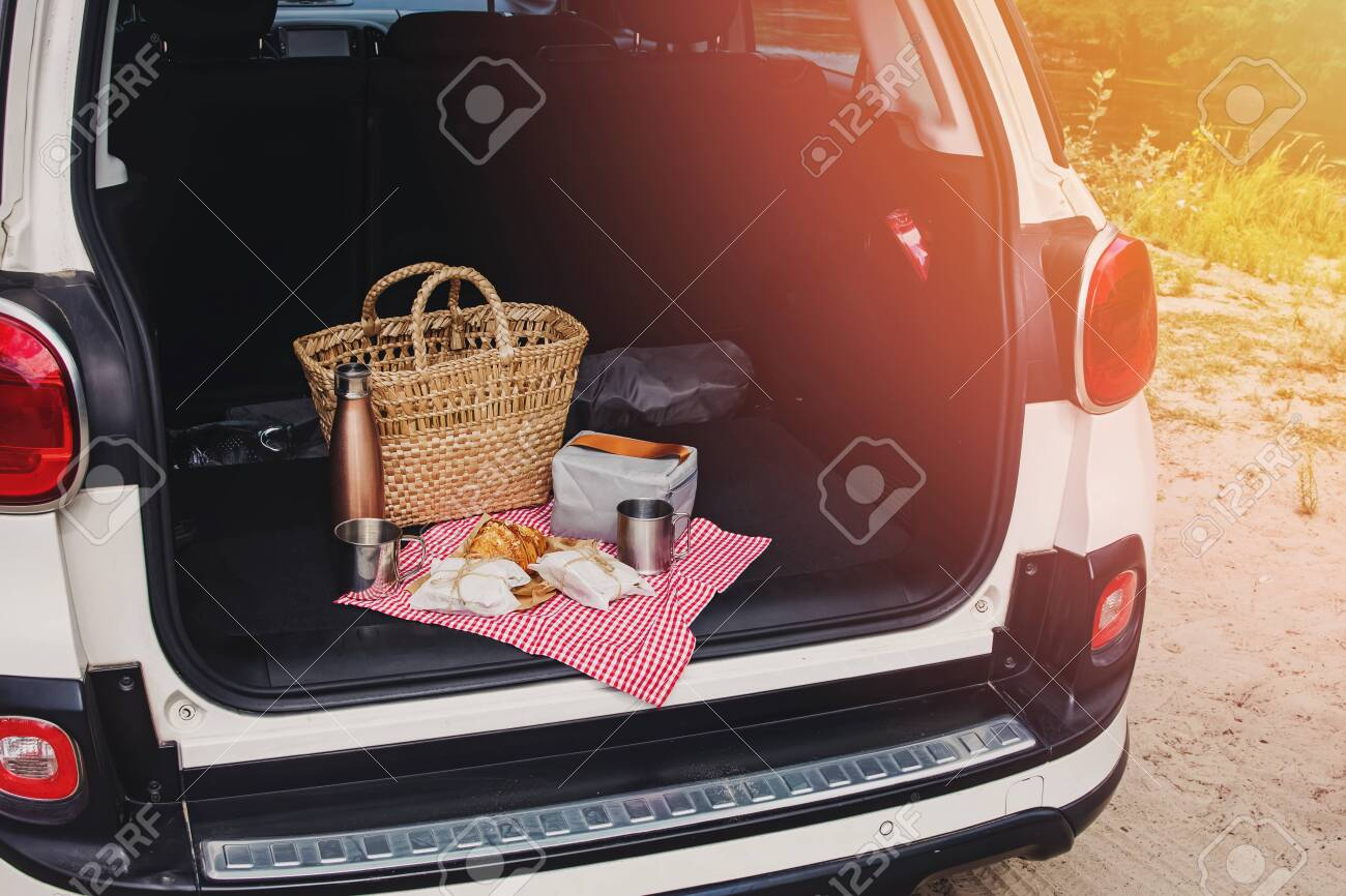 Picnic Package and Basket with Croissant and Sandwiches Lies on the in the trunk of hatchback car - 154871169