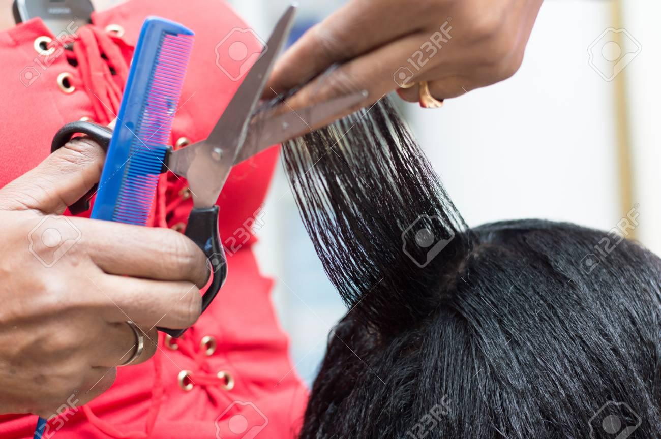 hairdresser arranges the hair of her customer by cutting with scissors em. Banque d'images - 70199585