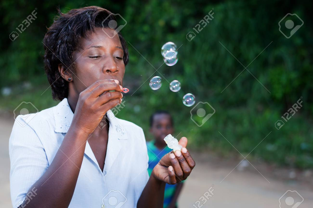 pretty young woman blowing bubbles and her child looks in the background. Banque d'images - 87697711