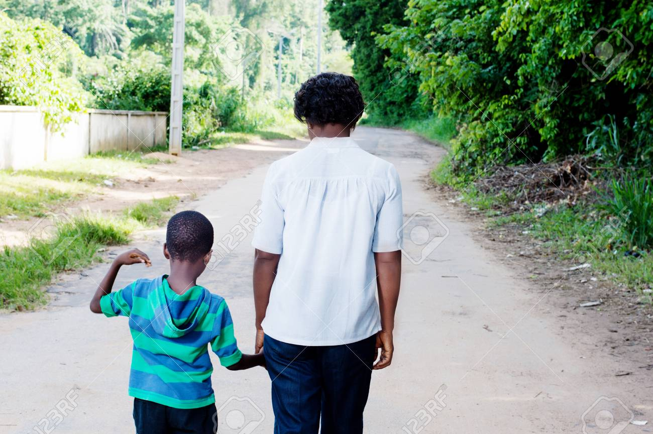 Young woman holding the hand of her child and walk on the country road. Banque d'images - 87697713