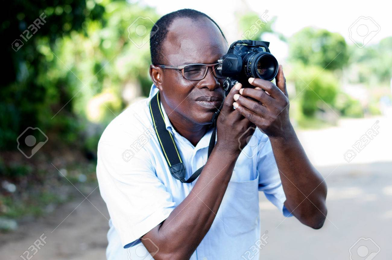 people, photography, entertainment and lifestyle - happy young man holding a digital camera and taking pictures on the street of the campaign Banque d'images - 87492719