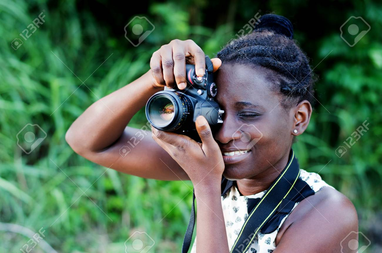Travel, tourism and hobby. Young woman photographer taking pictures in the bush. Banque d'images - 87549503
