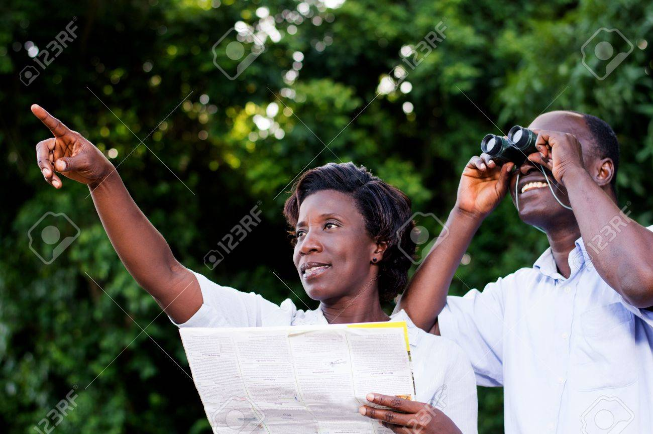 young woman pointing at the young man looking through binoculars. Banque d'images - 87723996