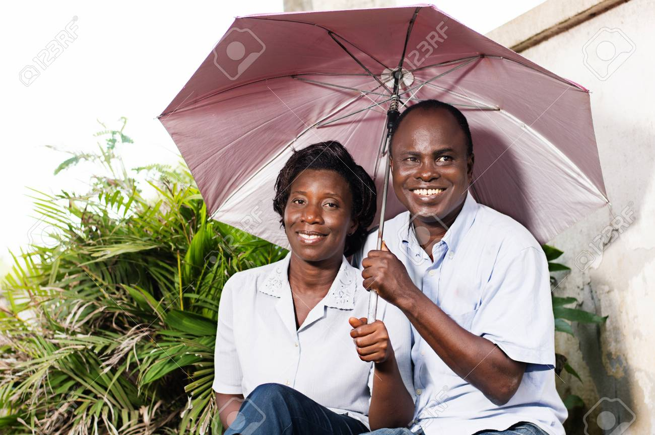 happy adult couple sitting and protecting themselves with an umbrella near a flower. Banque d'images - 95623089