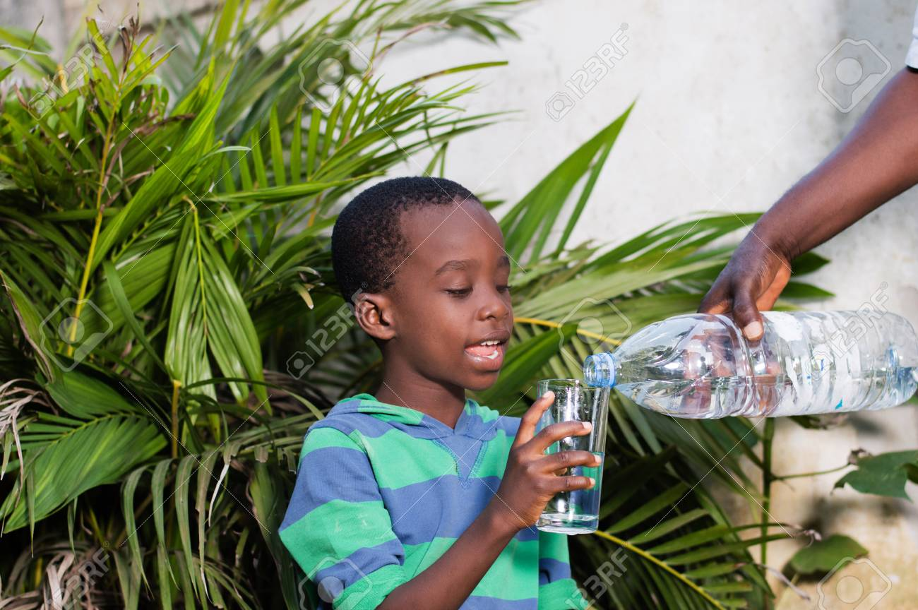 smiling little boy holding a glass of water in which they serve him water. Banque d'images - 96858569