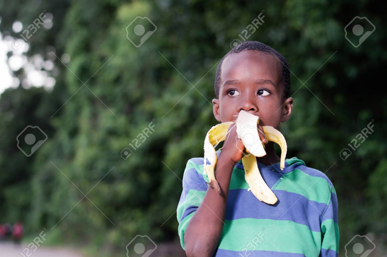 happy little boy eating a banana. Banque d'images - 96838340