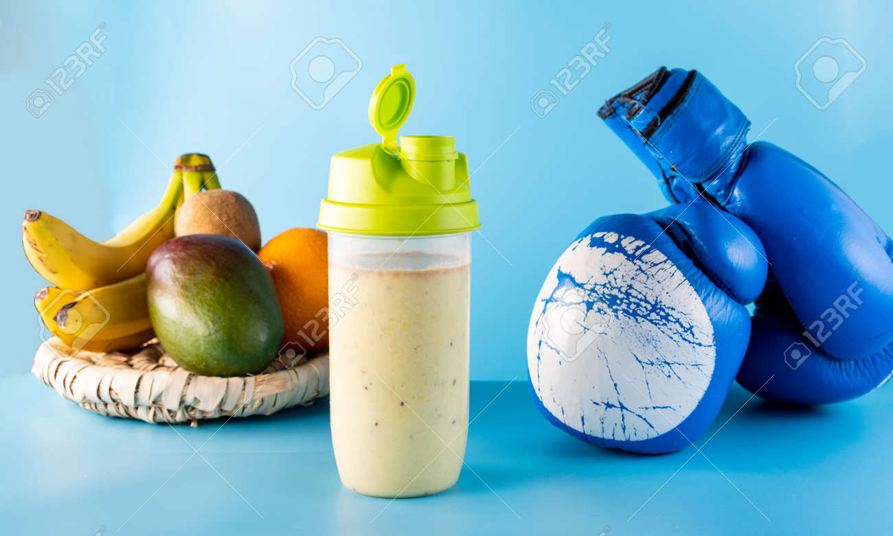 Vitamin protein sports nutrition. Multivitamin food from fruits. Milk cocktail and boxing gloves. Blue background. - 168666209