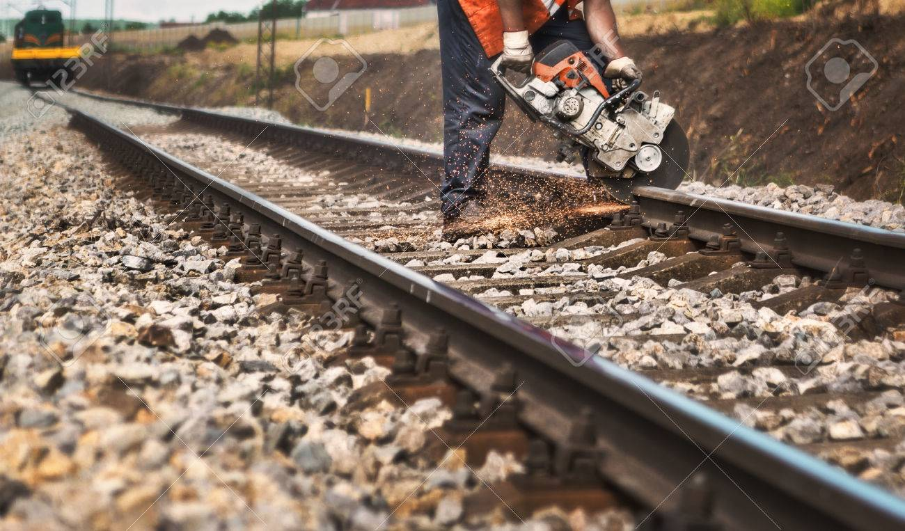 Reconstruction of the railway -Worker on the railway cuts rail with a machine - 64857220