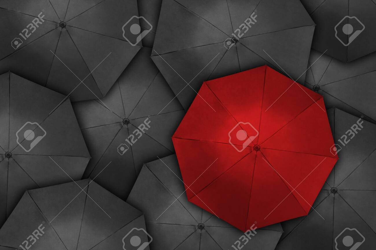 Standing out from the crowd, high angle view of red umbrella over many dark ones - 144582467
