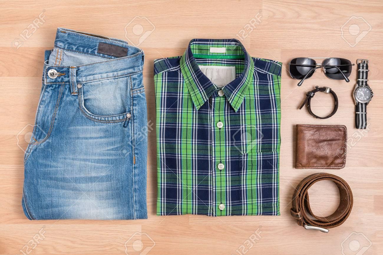 d73a415e8033 Los hombres clásicos equipos ocasionales de moda con accesorios de mesa de  madera, azul y camisa verde a cuadros y pantalones vaqueros con anteojos,  ...