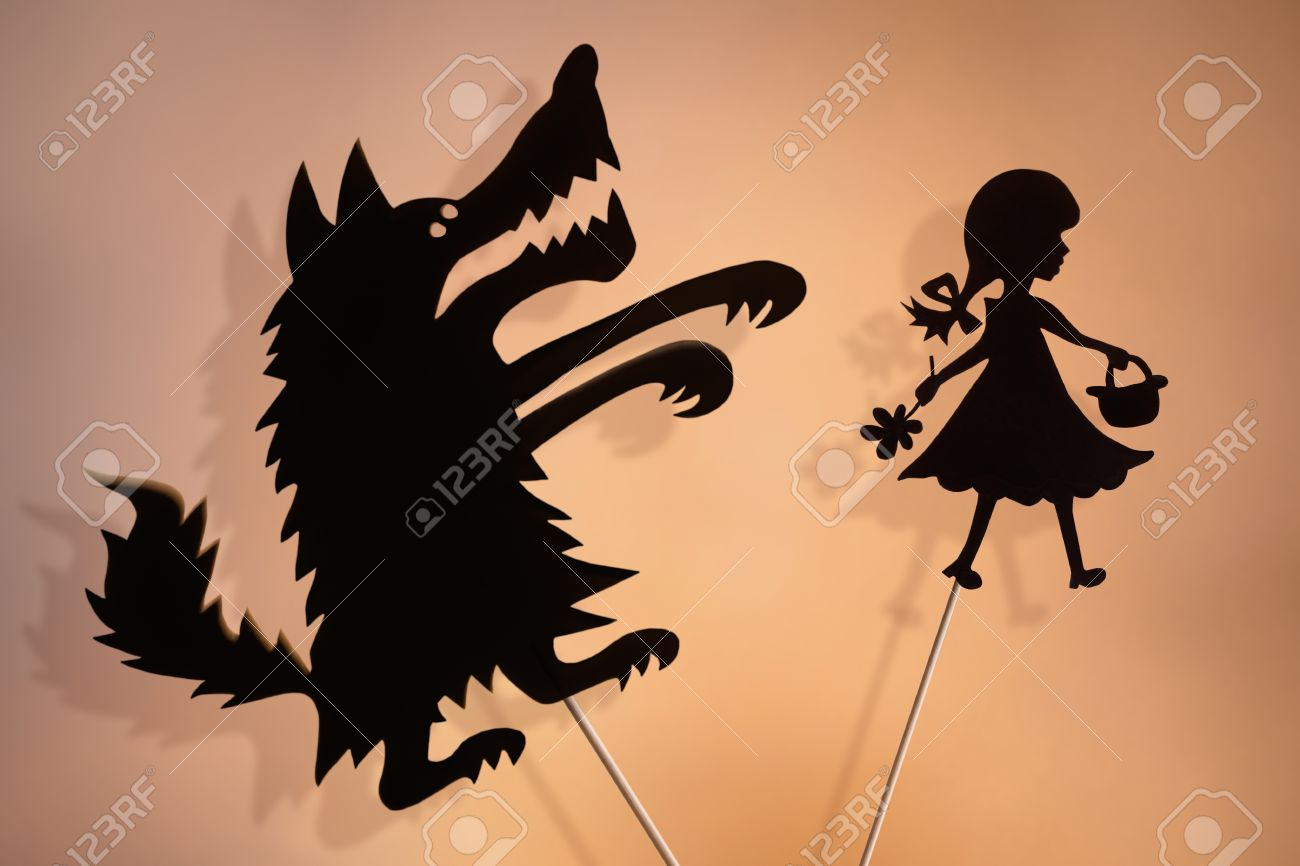Little Red Riding Hood and the Big Bad Wolf shadow puppets and their shades on the soft glowing screen of shadow theater. - 54478506
