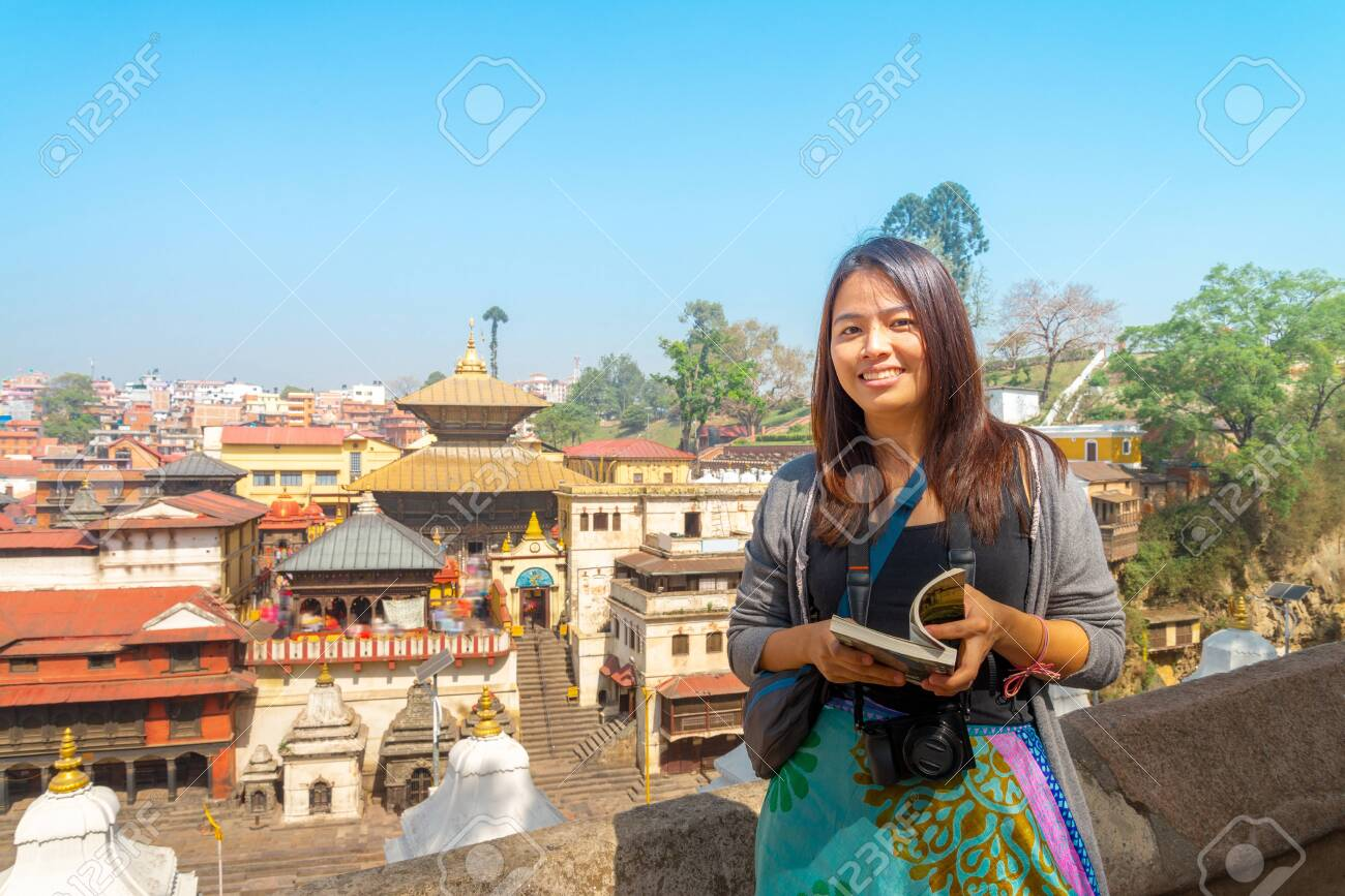 An asian tourist visited the Pashupatinath Temple is a famous Located on the banks of the Bagmati River in Kathmandu, Nepal. - 128411598