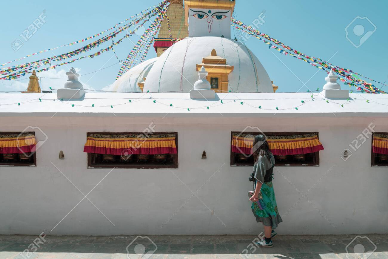 An asian women tourist touch the bell inside the wall of Boudhanath Stupa and praying get blessing at Kathmandu, Nepal. - 128411618