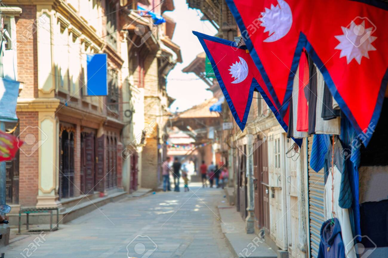 The Nepal national flag in foreground decoration in front of nepali house and the background is perspective of village in Kathmandu Nepal. - 128411959