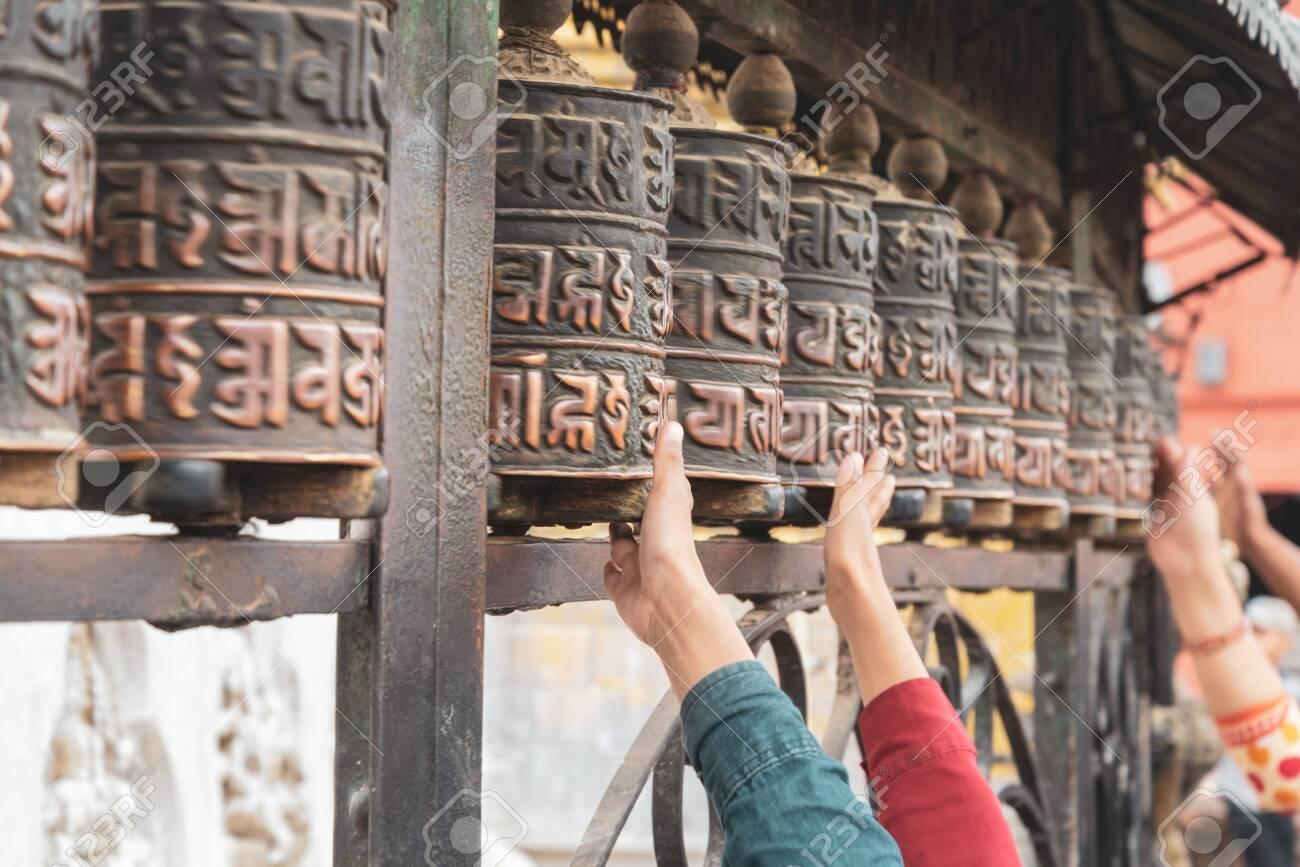 Tibetan prayer wheels at Swayambhunath, Nepal. Text translation: The magic symbol power of buddhism for prayer get divine blessings and good fortune. - 128411958