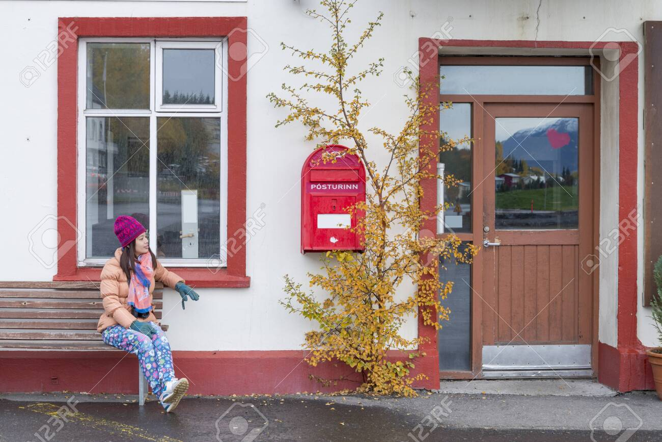 Women tourist looking the red old mailbox in Iceland. - 136156172