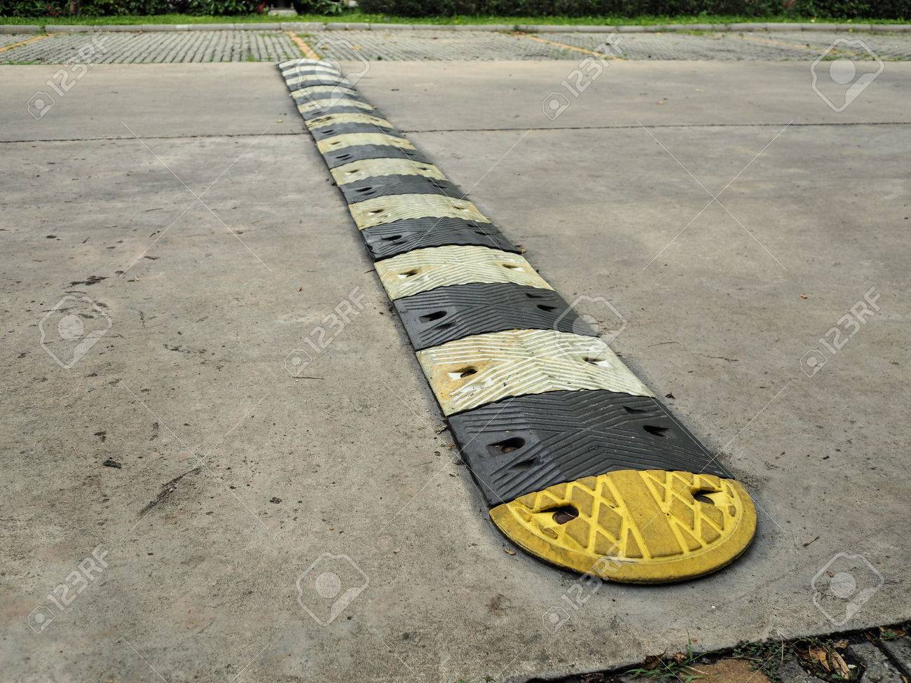 An old pale yellow and black traffic safety speed bump on a concrete road  at parking