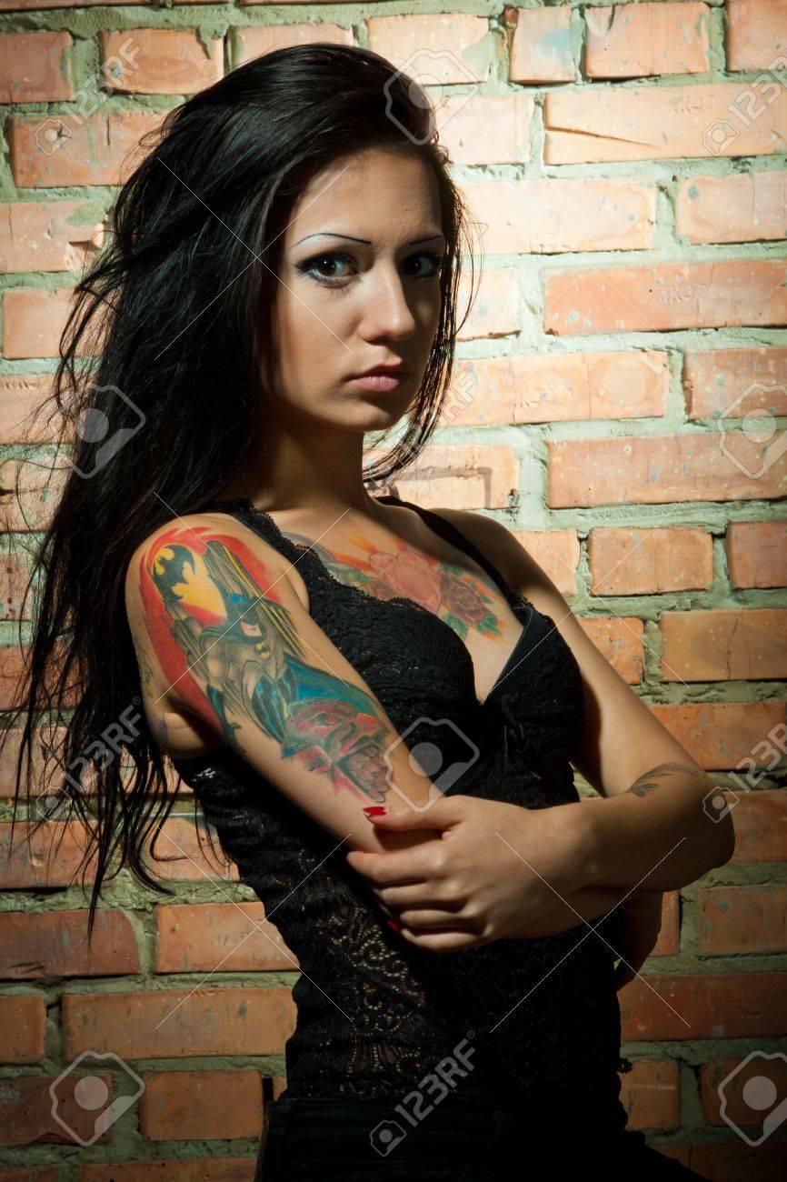 Chica Sexi Bruna Tatuado En El Fondo De Brickwall Mirando La Cámara