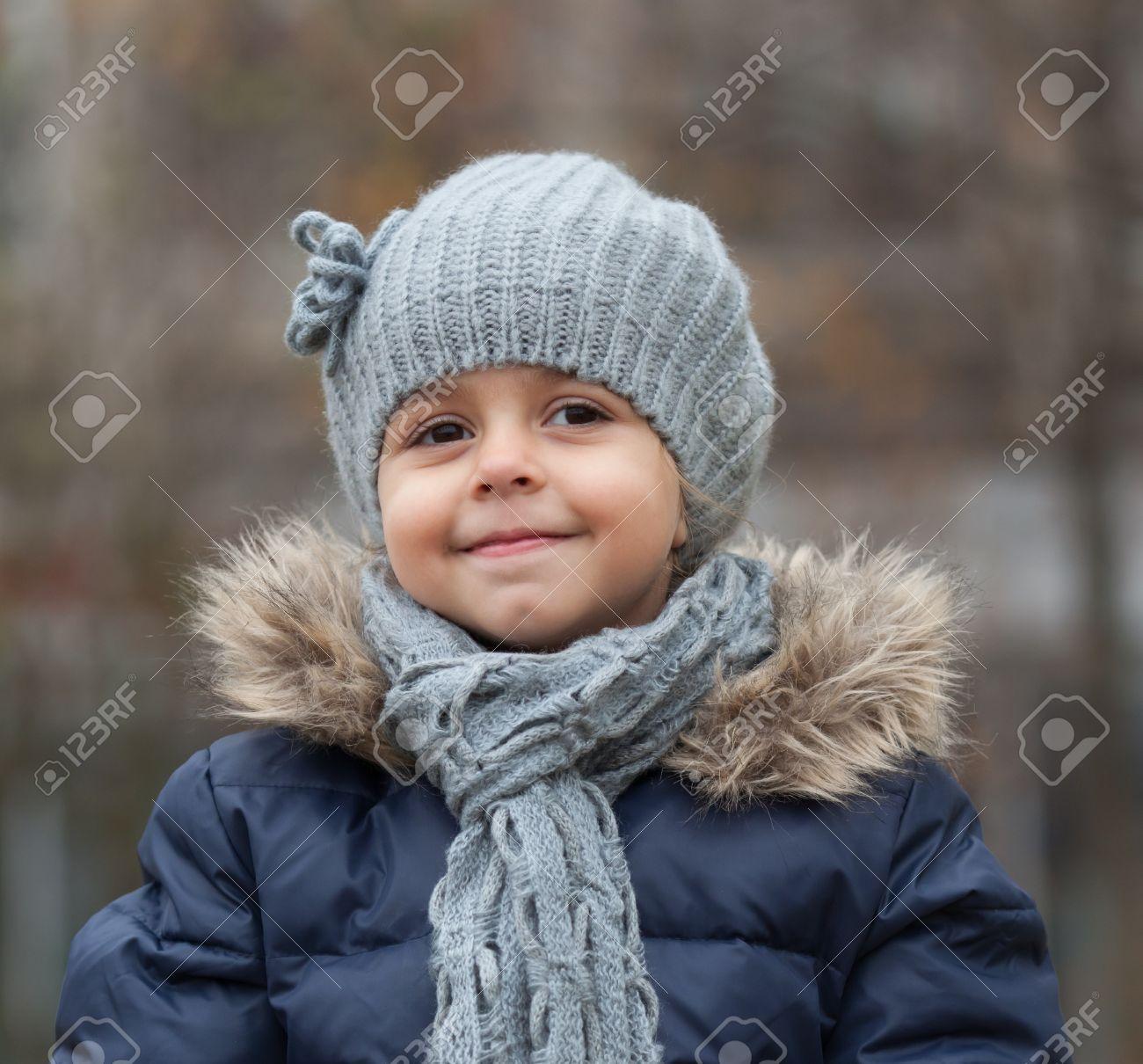 f82da166a8aba Foto de archivo - Retrato de la sonrisa niña con gorro de lana y bufanda.