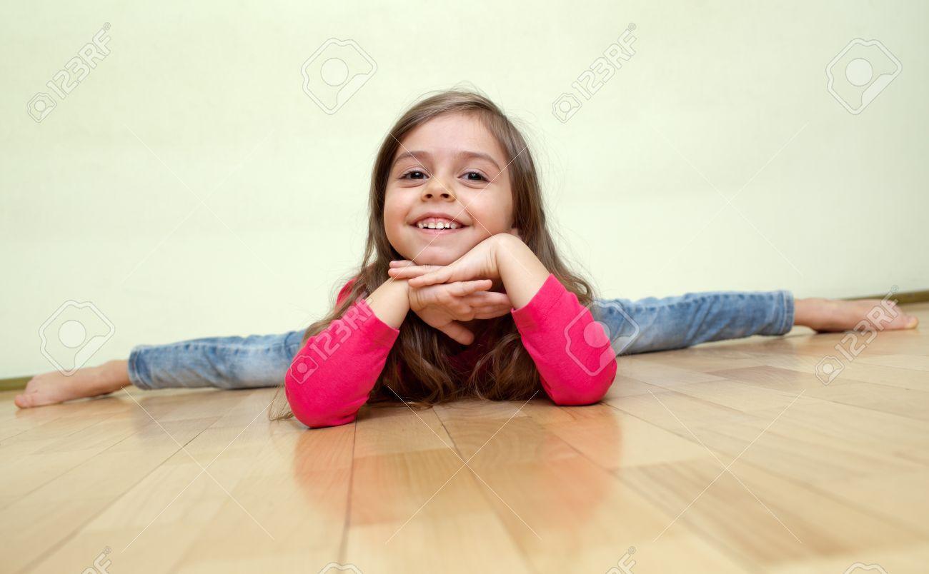 Five year old girl do leg-split (Front splits) smiling, wearing