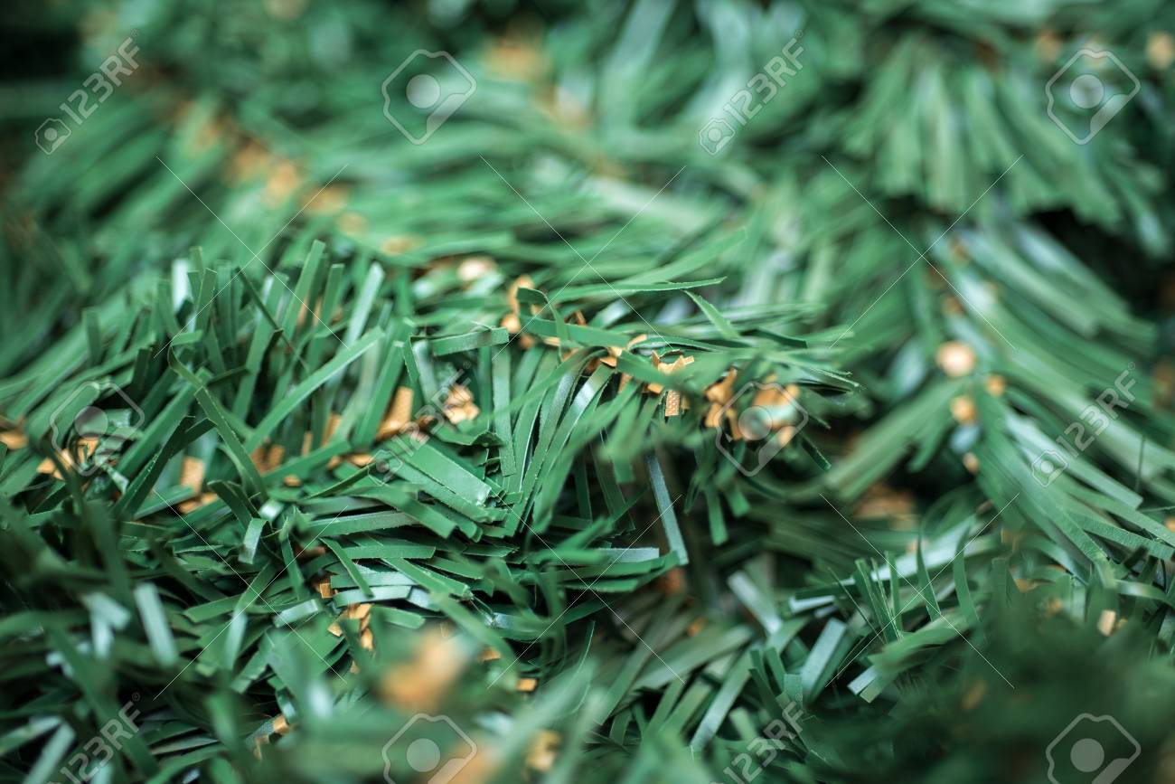 Artificial Christmas Tree Branches.Background Of Green Artificial Christmas Tree Branches