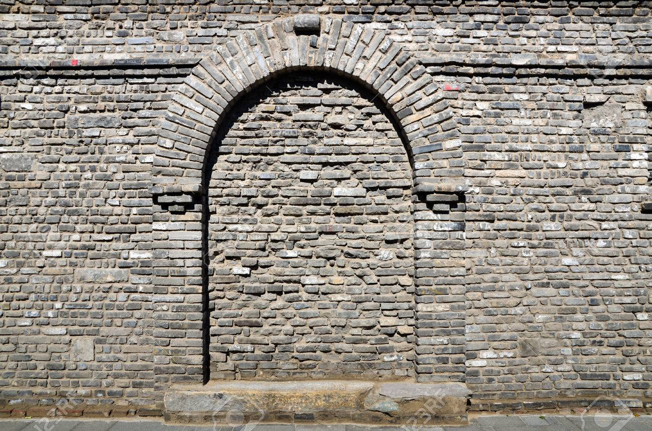 A Gray Brick Wall The Shape Of A Door On It The Garden Arch