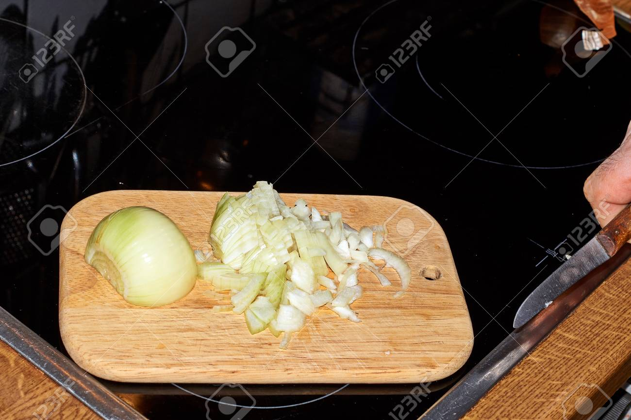 Chef Slicing Onion Allium Cepa On The Cutting Board With A Knife