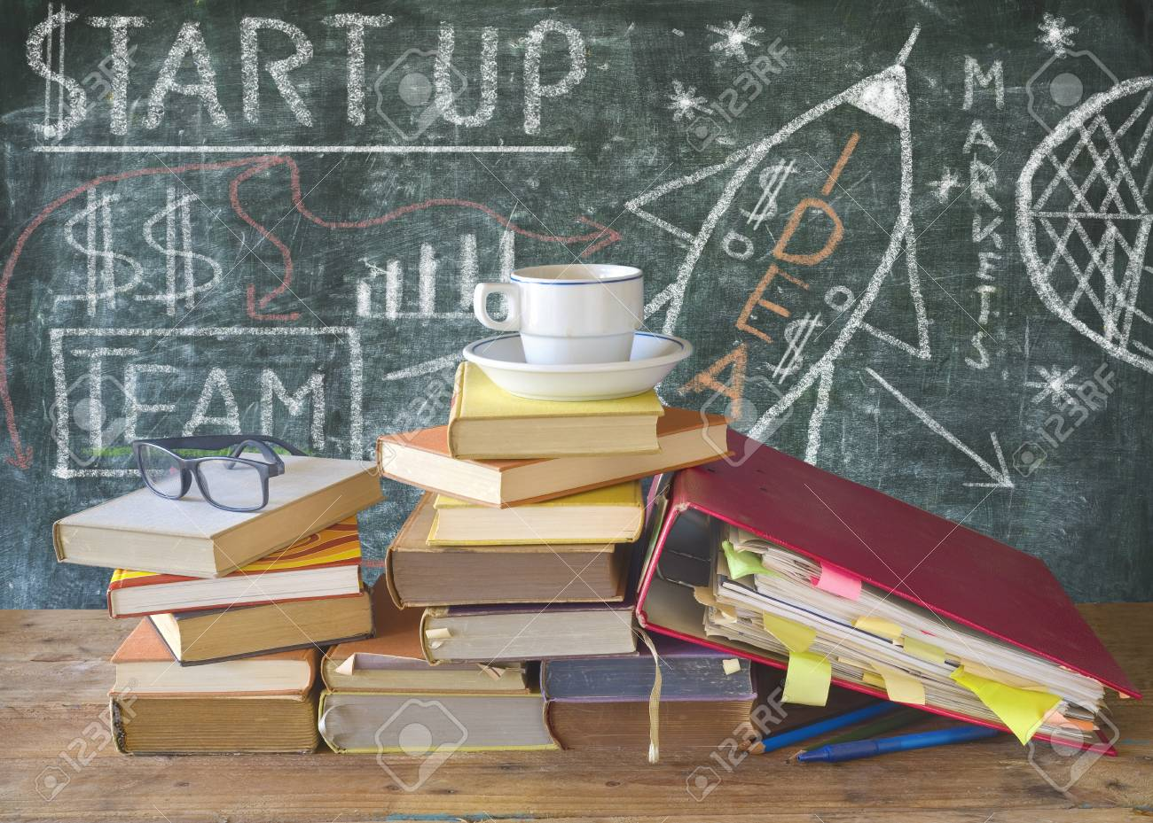 drawing of a start up concept on chalkboard w books file folders