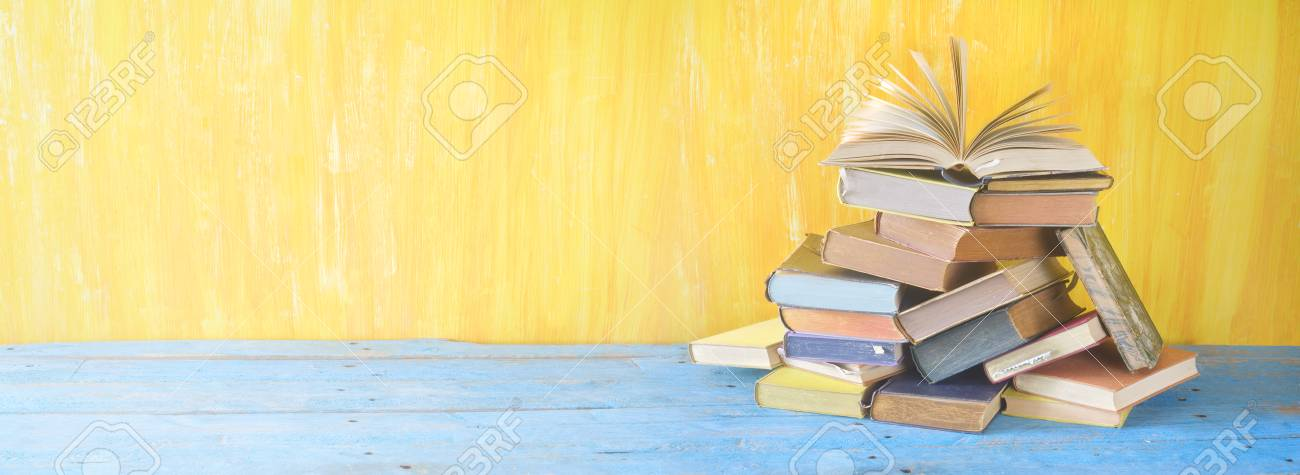 Opened book on a pile of books, panorama, good copy space - 96903508