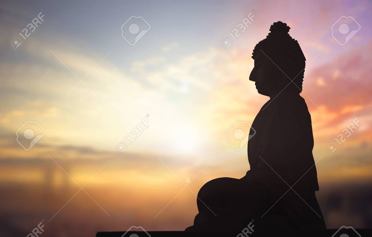 Silhouette of Buddha statue against sunset background - 121740509