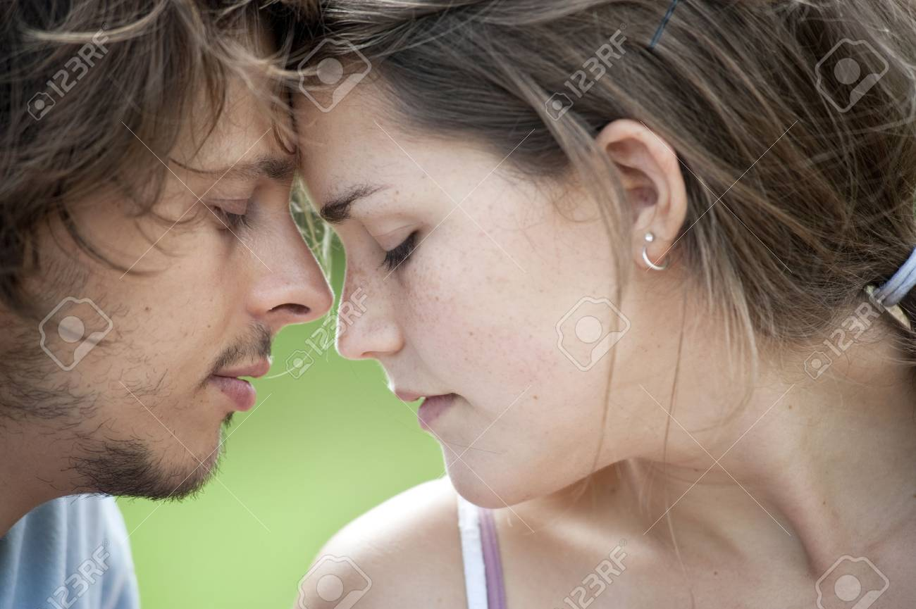 Young couple in love sit in a park and enjoy the sunshine together. Stock Photo - 6520567