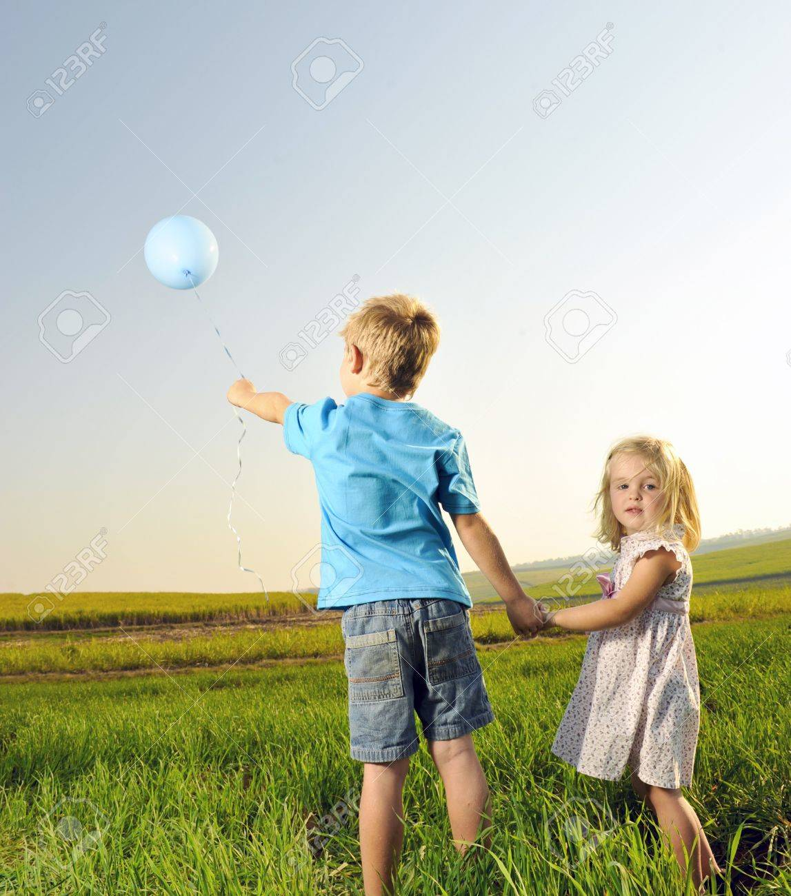 Brother and sister hold hands and hold onto their only balloon Stock Photo - 7378843