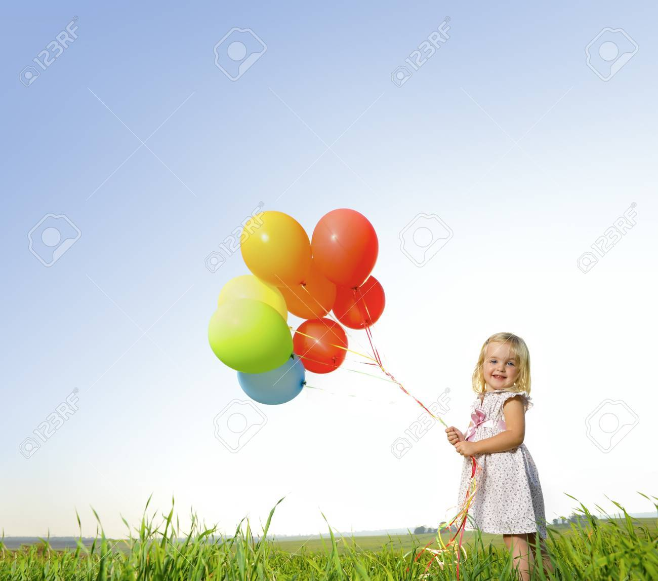 Adorable young girl holds tightly to a large bunch of helium filled balloons Stock Photo - 7378833
