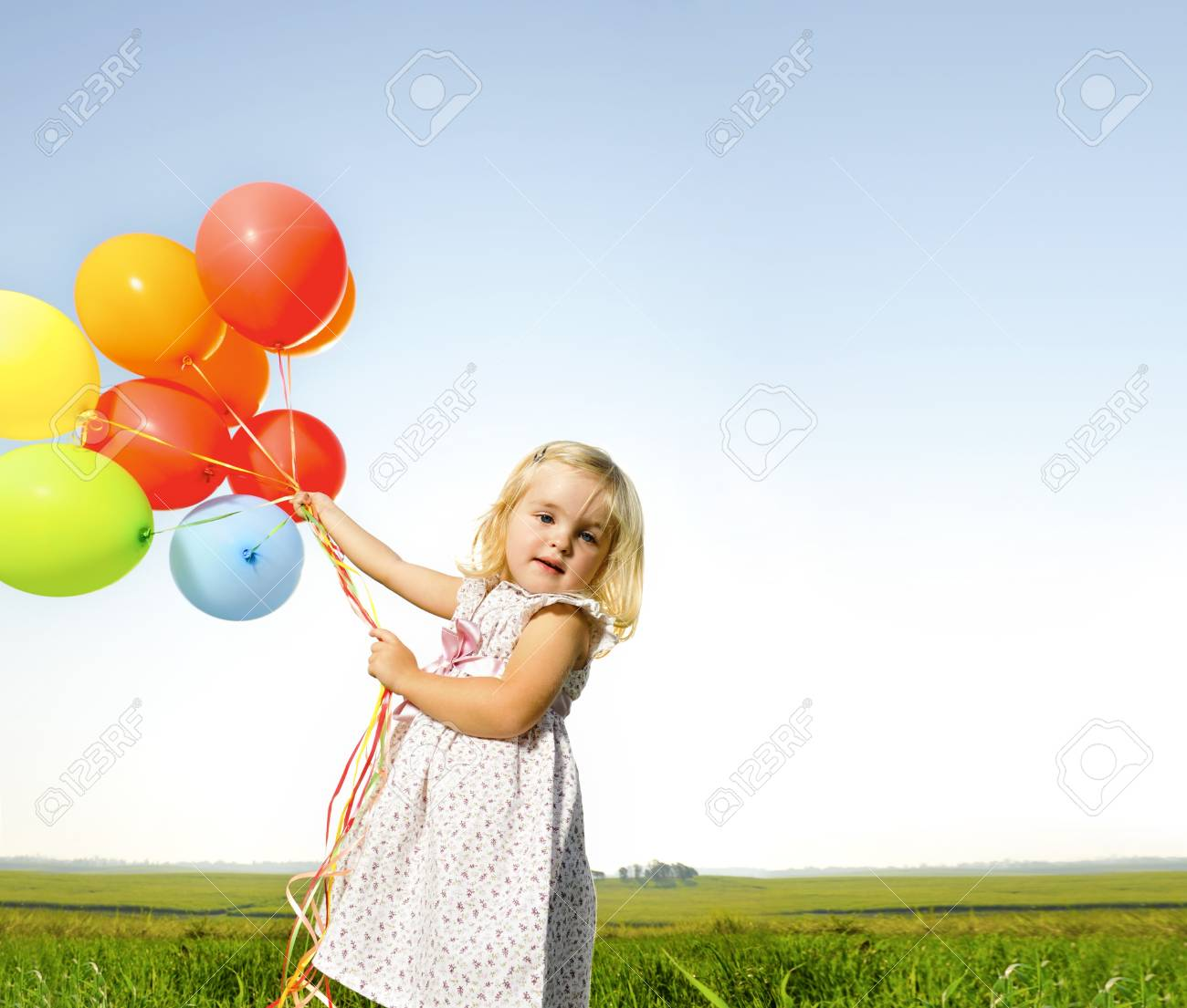 Adorable young girl holds tightly to a large bunch of helium filled balloons Stock Photo - 7378841