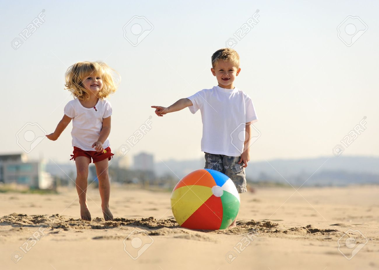Beautiful brother and sister play with a beach ball outdoors Stock Photo - 7785530