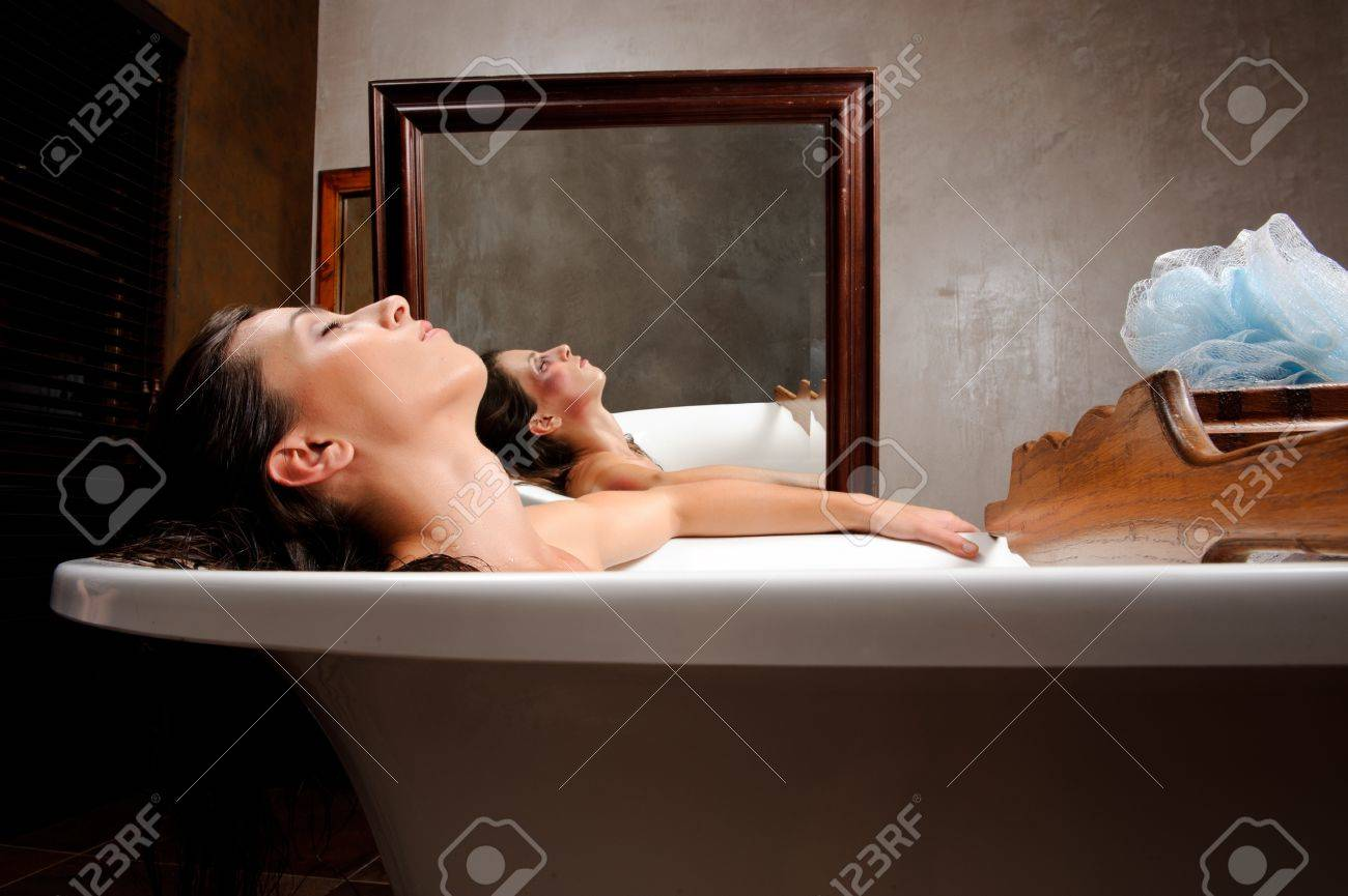 Woman relaxing in bathtub with mirror image of her with bruises on her face, a conceptual shoot of domestic abuse often hidden from public Stock Photo - 8726738