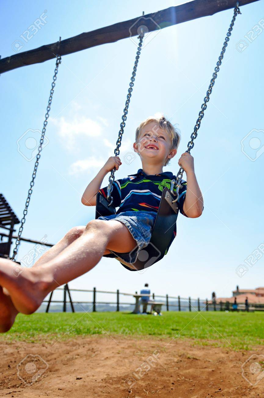 Young child plays on swing in the outdoor playground Stock Photo - 8726885